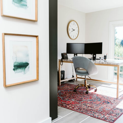 green and white mudroom/office space with marble top desk and green builtins